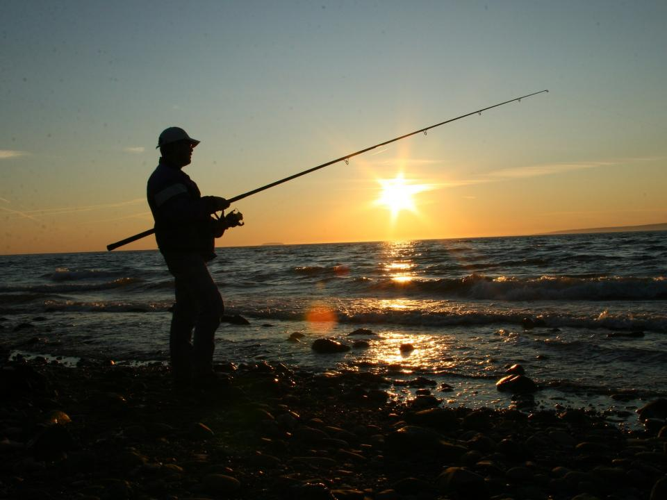 The silhouette of a man is fishing by the seaside