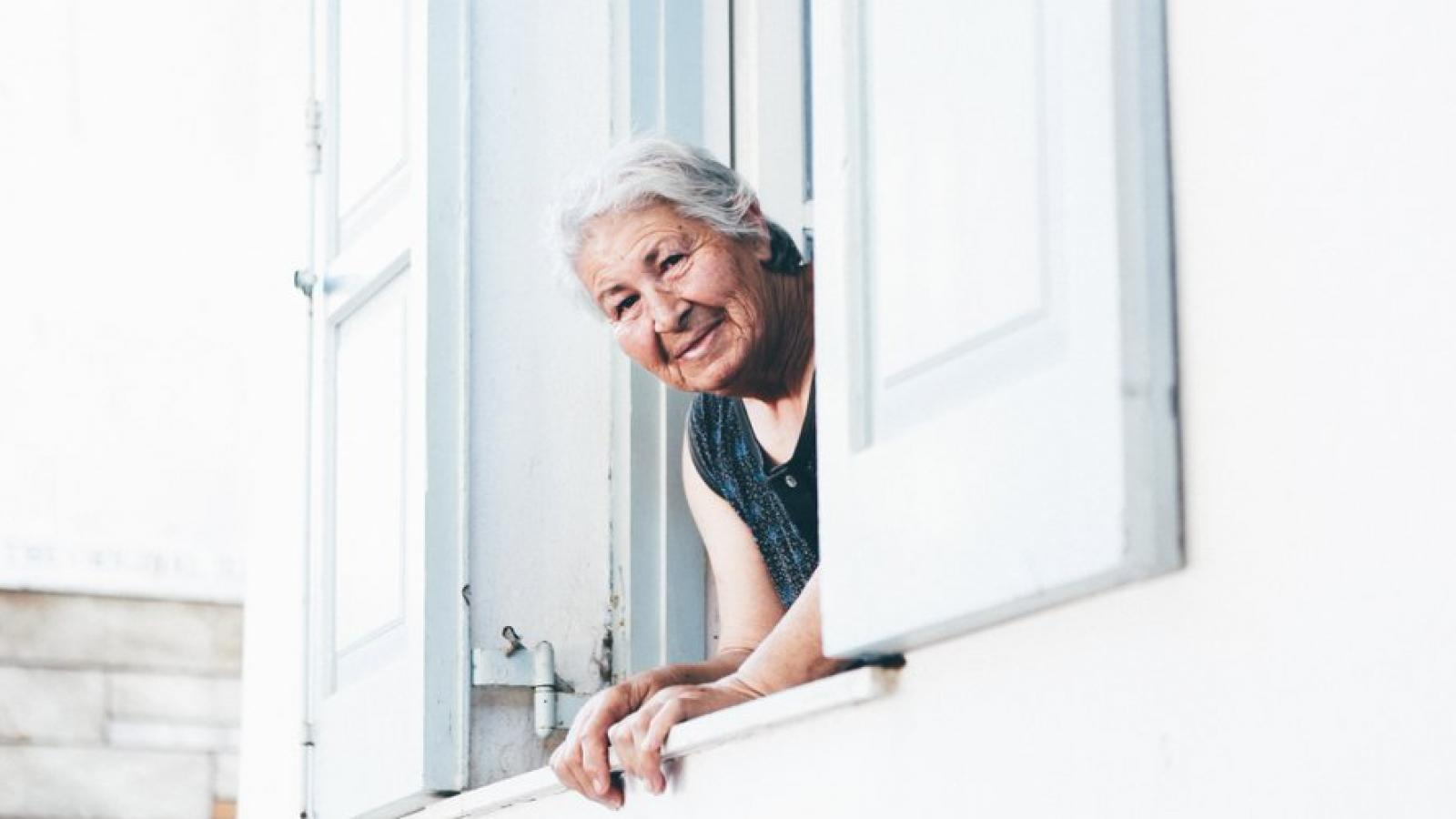 An old lady leans out of a house window and is looking at the camera