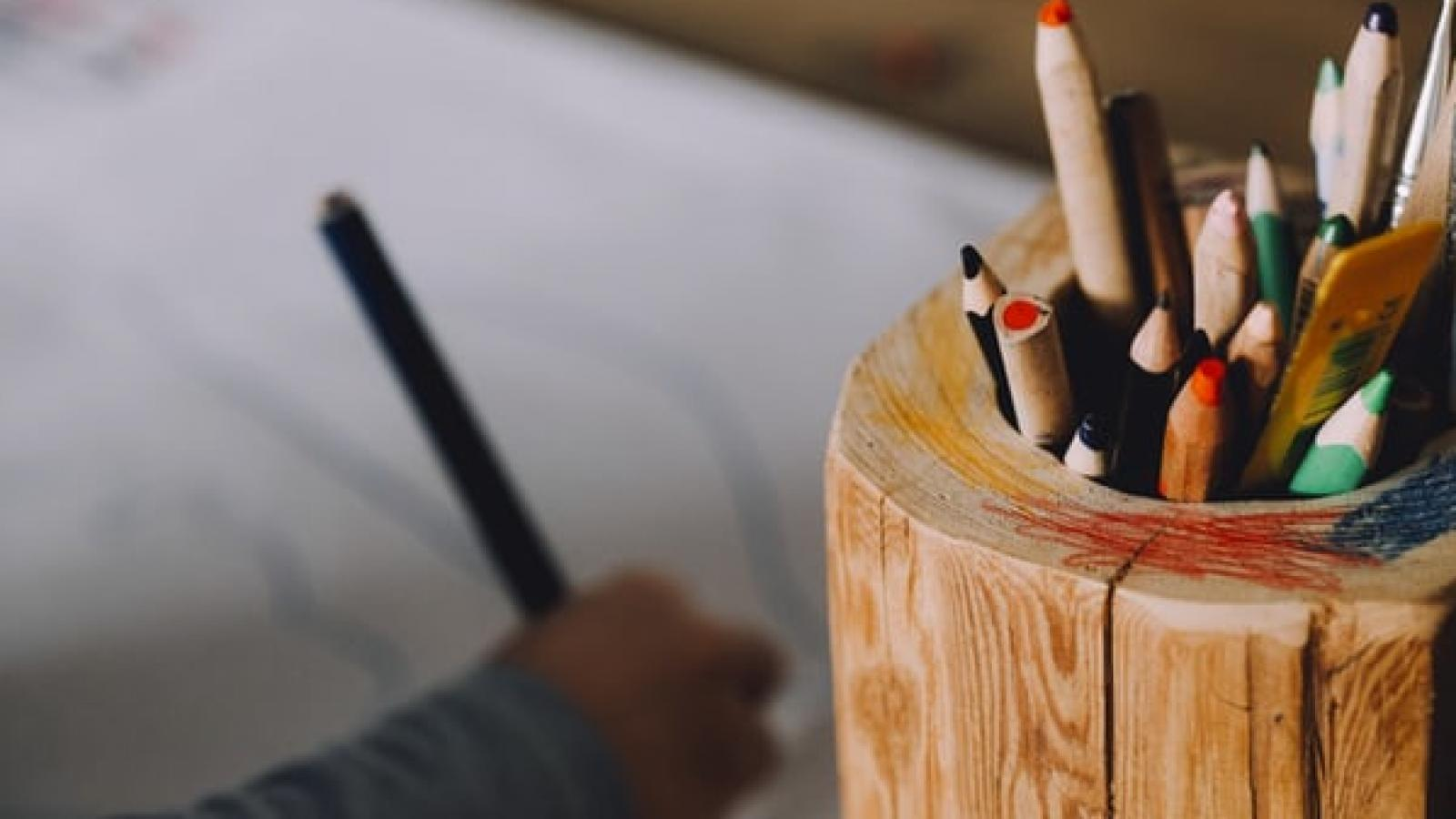 A carton of colouring pencils sits to the right of a child's hand drawing