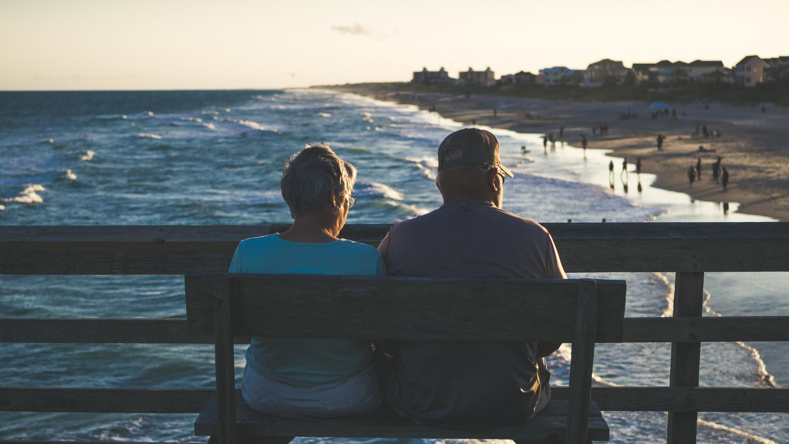 A couple sit with their backs to the camera on a bench overlooking a beach