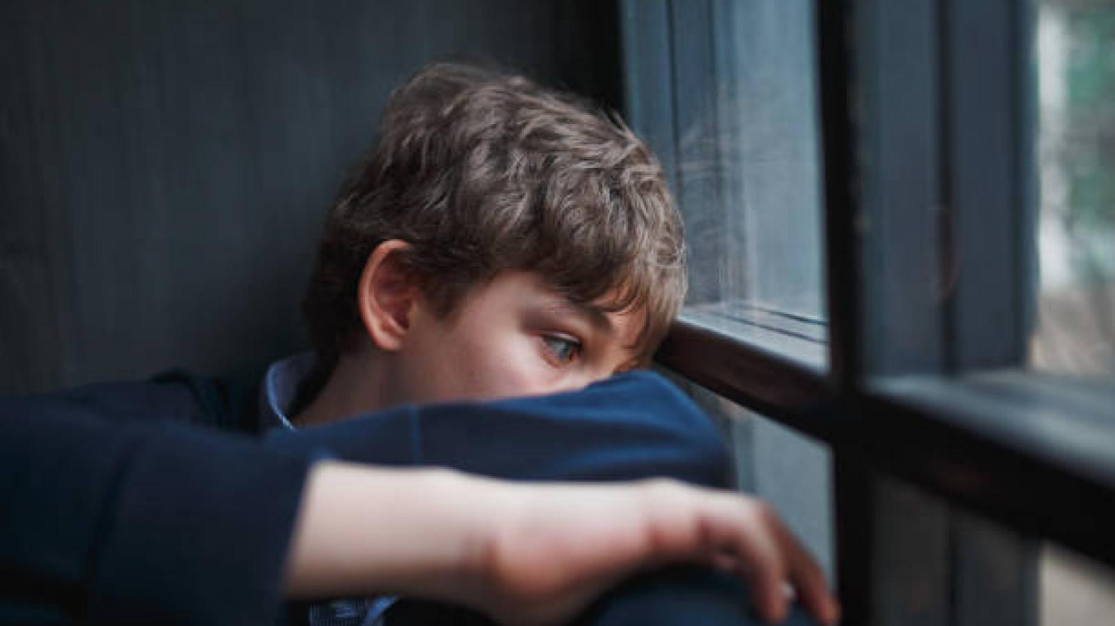 A young boy looks sad whilst looking out a window